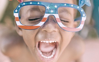 Little boy laughing with American flag glasses