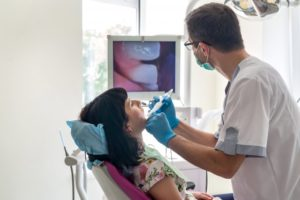 dentist examining patient's mouth with intraoral camera