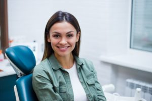 a woman sitting in the dentist chair smiling
