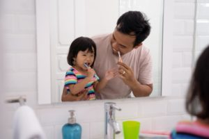 parent brushing their teeth next to their child