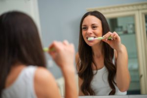 a young woman with dark hair standing in front of the bathroom mirror brushing her teeth